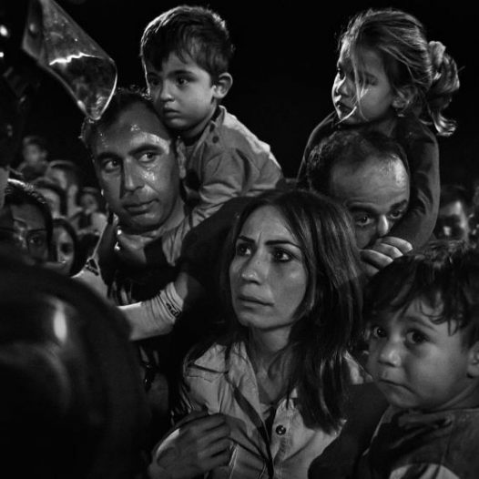 A family of migrants waits at night at the Tovarnik, Croatia train station. As borders opened and closed, asylum seekers struggled to find a safe route through Europe. September 17, 2015  James Nachtwey for TIME