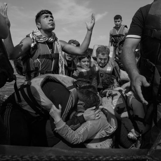 Refugees celebrate after arriving on the beach in Lesbos, Greece. Thousands of migrants each day set out from nearby Turkey for the Greek island, riding in barely seaworthy rubber boats. Some don't make it, September 26, 2015. James Nachtwey for TIME