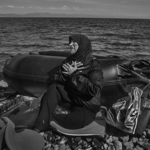 Leaving behind everything they've ever known, migrants arrive on the beach in Lesbos, Greece with little or no possessions. A woman sits on the beach recovering  from the sea journey in an inflatable boat, September 27, 2015. James Nachtwey for TIME