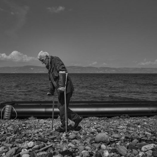 A man walks with crutches on the beach in Lesbos, Greece after arriving on an inflatable boat from Turkey, September 25, 2015.   James Nachtwey for TIME
