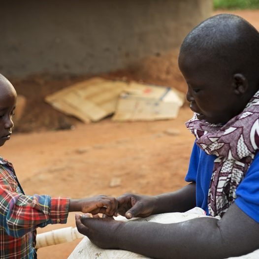 Breast Cancer patient Jessy Acen, from Gulu, plays tenderly with one of her sons, Jered Kakanyero, 4, as he caresses her swollen arm and hand in Pece Vanguard, on the outskirts of Gulu, Uganda, July 23, 2013.  Jessy Acen first discovered a lump in her breast in 2009. She traveled from her home in Gulu to Mulago Hospital in the Ugandan capital of Kampala to have her diagnosis of breast cancer confirmed. She began chemotherapy soon after but, unable to afford the cost of transport the 300 km from Gulu to Kampala, she was forced to stop treatment. By the time she'd returned to Mulago in 2011 her cancer had spread to her lymph nodes, liver and lungs. (Credit: Lynsey Addario for The New York Times)