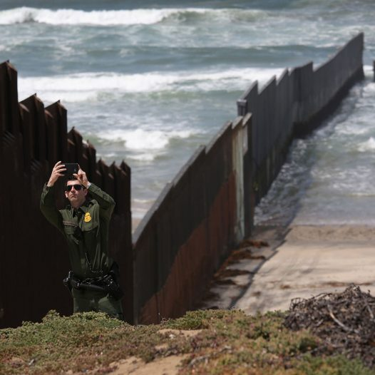 SAN DIEGO, CA - APRIL 30:  A U.S. Border Patrol agent takes a selfie at the U.S.-Mexico border fence on April 30, 2016 into San Diego, California. Five families, with some members living in Mexico and others in the United States, were permitted to meet and embrace for three minutes each at a door in the fence, which the U.S. Border Patrol opened to celebrate Mexican Children's Day. It was only the third time the fence, which separates San Diego from Tijuana, had been opened for families to briefly reunite.  (Photo by John Moore/Getty Images)
