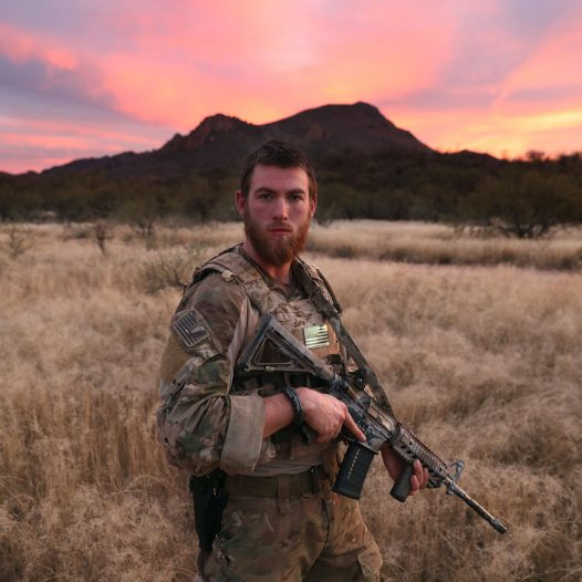 "PIMA COUNTY, AZ - NOVEMBER 16:  Civilian paramilitary volunteer James, 24,  for Arizona Border Recon (AZBR), stands near the U.S.-Mexico border on November 16, 2016 in Pima County, Arizona. The college student said he felt it is his duty to help protect the nation's borders. ""There's evil going on here,""he said. AZBR is made up mostly of former U.S. military servicemen, stages reconnaissance and surveillance operations against drug and human smugglers in remote border areas. The group claims up to 200 volunteers and does not consider itself a militia, but rather a group of citizens supplimenting U.S. Border Patrol efforts to control illegal border activity. With the election of Donald Trump as President, border security issues are a top national issue for the incoming Administration.  (Photo by John Moore/Getty Images)"