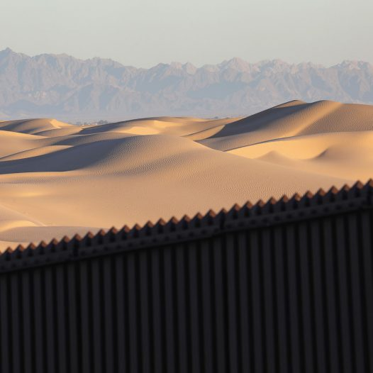 "FELICITY, CA - NOVEMBER 17: Mexico is seen over the U.S.-Mexico border fence at the Imperial Sand Dunes on November 17, 2016 near Felicity, California. The 15-foot border fence there, also known as the ""floating fence,"" sits atop the dunes and moves with the shifting sands. Border Patrol agents say they catch groups of illegal immigrants and drug smugglers crossing in from Mexico there daily, despite the forbidding terrain.  (Photo by John Moore/Getty Images)"