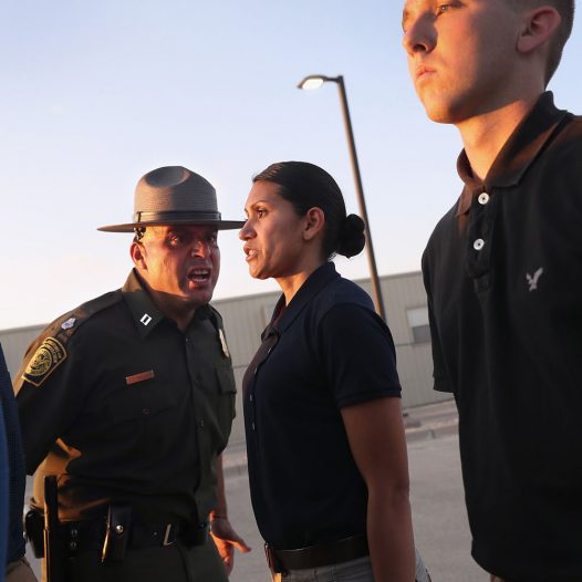 ARTESIA, NM - AUGUST 02:  A U.S. Border Patrol instructor yells at a new trainee run upon her initial arrival with fellow agents to the U.S. Border Patrol Academy on August 2, 2017 in Artesia, New Mexico. All new agents must complete a months-long training course at the New Mexico facility before assuming their posts at Border Patrol stations, mostly along the U.S.-Mexico border. President Trump has pledged to add an additional 5,000 agents to the existing Border Patrol force of more than 21,000 as part of his border security policy.  (Photo by John Moore/Getty Images)