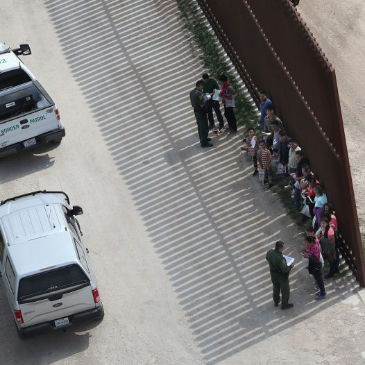 MCALLEN, TX - FEBRUARY 21:  U.S. Border Patrol agents question undocumented immigrant families at the U.S.-Mexico border fence while taking them into custody on February 21, 2018 near McAllen, Texas. A group of men, women and children from Central America were picked up after crossing the Rio Grande into Texas, seeking political asylum in the United States.  (Photo by John Moore/Getty Images)