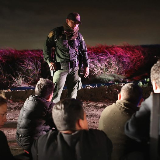 MCALLEN, TX - FEBRUARY 23:  A U.S. Border Patrol agent watches over a group of undocumented immigrants on February 23, 2018 in McAllen, Texas. The agents captured the group of Central American immigrants shortly after they rafted across the border from Mexico into Texas. (Photo by John Moore/Getty Images)