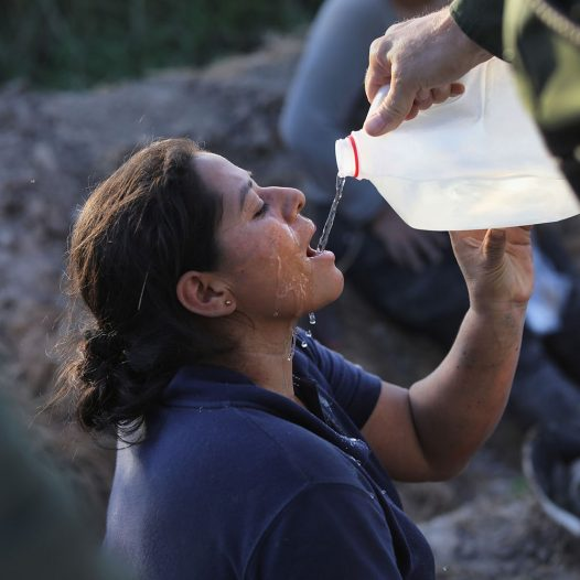 "MISSION, TX - JUNE 12:  An undocumented immigrant is given water by U.S. Border Patrol agents after she was aprehended in a sugarcane field near the U.S.-Mexico Border on June 12, 2018 near Mission, Texas. U.S. Customs and Border Protection (CBP) is executing the Trump administration's ""zero tolerance"" policy towards undocumented immigrants. U.S. Attorney General Jeff Sessions also said that domestic and gang violence in immigrants' country of origin would no longer qualify them for political asylum status.  (Photo by John Moore/Getty Images)"