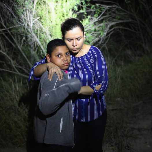 "MCALLEN, TX - JUNE 12:  A U.S. Border Patrol spotlight shines on a terrified mother and son from Honduras as they are found in the dark near the U.S.-Mexico border on June 12, 2018 in McAllen, Texas. The asylum seekers had rafted across the Rio Grande from Mexico and had become lost in the woods. They were then detained by Border Patrol agents and then sent to a processing center for possible separation. Customs and Border Protection (CBP) is executing the Trump administration's ""zero tolerance"" policy towards undocumented immigrants. U.S. Attorney General Jeff Sessions also said that domestic and gang violence in immigrants' country of origin would no longer qualify them for political asylum status.  (Photo by John Moore/Getty Images)"