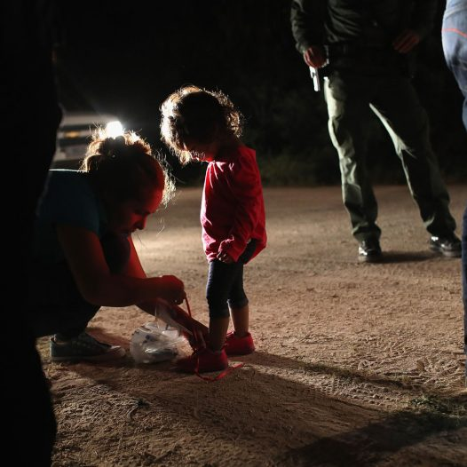 """MCALLEN, TX - JUNE 12:  A Honduran mother removes her two-year-old daughter's shoe laces, as required by U.S. Border Patrol agents, after being detained near the U.S.-Mexico border on June 12, 2018 in McAllen, Texas. The asylum seekers had rafted across the Rio Grande from Mexico and were detained by federal authorities before being sent to a processing center for possible separation. Customs and Border Protection (CBP) is executing the Trump administration's """"zero tolerance"""" policy towards undocumented immigrants. U.S. Attorney General Jeff Sessions also said that domestic and gang violence in immigrants' country of origin would no longer qualify them for political asylum status.  (Photo by John Moore/Getty Images)"""