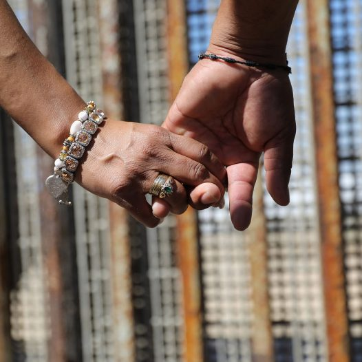 TIJUANA, MEXICO - SEPTEMBER 25: A couple holds hands while meeting loved ones through the U.S.-Mexico border fence on September 25, 2016 in Tijuana, Mexico. The U.S. Border Patrol opens the park on the American side in San Diego on weekends to meet through the fence with family and friends through the fence at Tijuana. The park is one of the few places on the 2,000-mile border where separated families are allowed to meet. (Photo by John Moore/Getty Images)